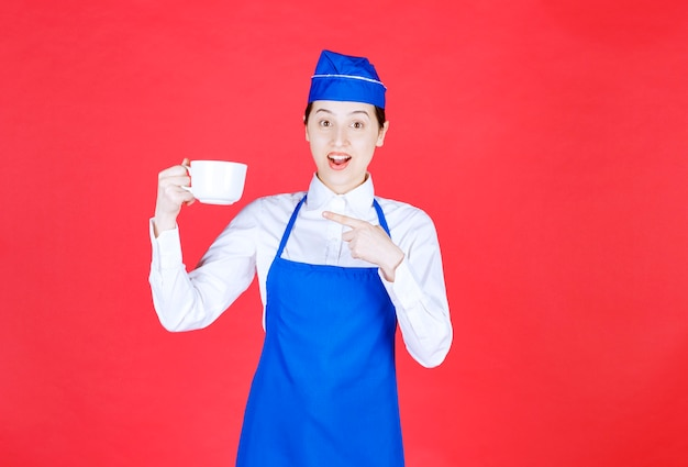Woman waitress in uniform standing and pointing at a cup on red wall .