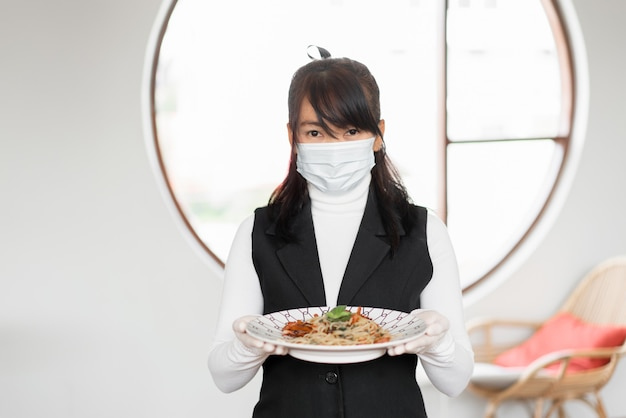 Woman waitress with face mask for working