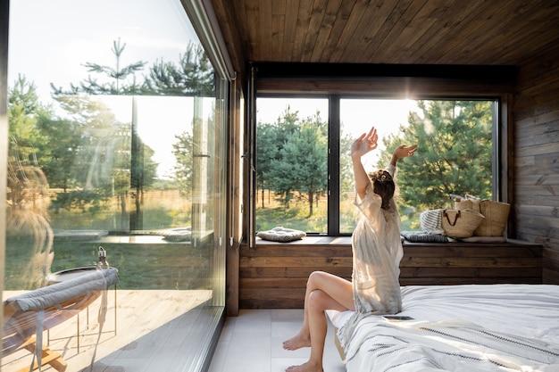Женщина просыпается в загородном доме на природе