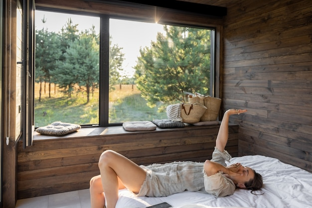 Женщина просыпается в загородном доме или отеле с панорамными окнами в сосновом лесу, зевая подняв руки. доброе утро и отдых на природе