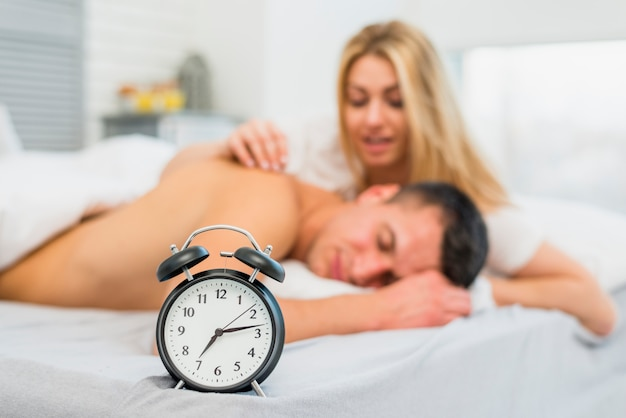 Woman waking up man near snooze in bed