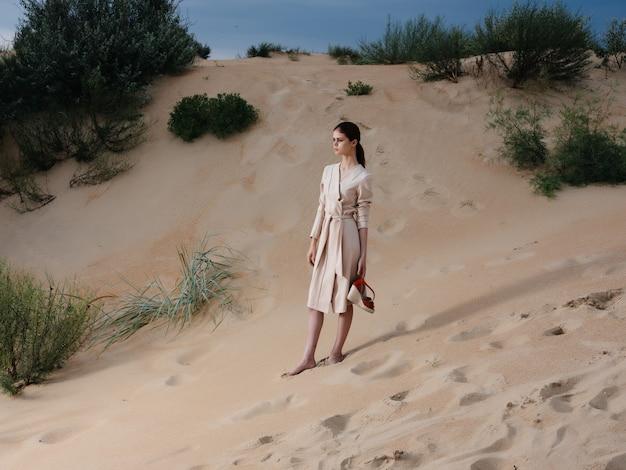 女性はビーチの砂の熱帯のエレガントなスタイルに沿って歩く