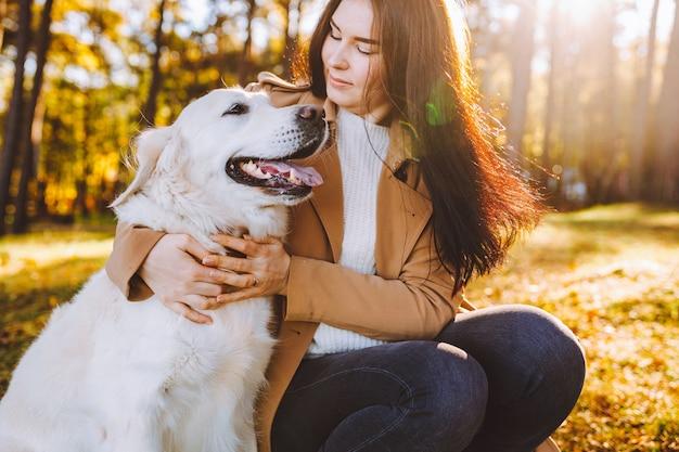 여자는 노란색 가을 공원에서 그녀의 골든 리트리버와 산책과 놀이