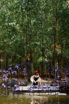 夏の春に美しい色でファンタジーフラワードリームフィールドを歩く女性。