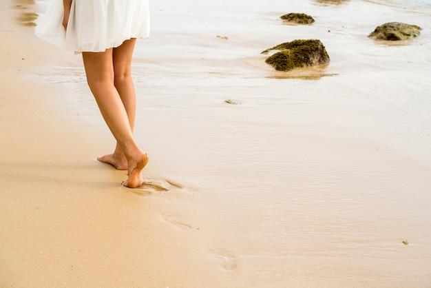 Женщина ходить по пляжу, печать ноги на текстуру песка, скопировать пространстве.