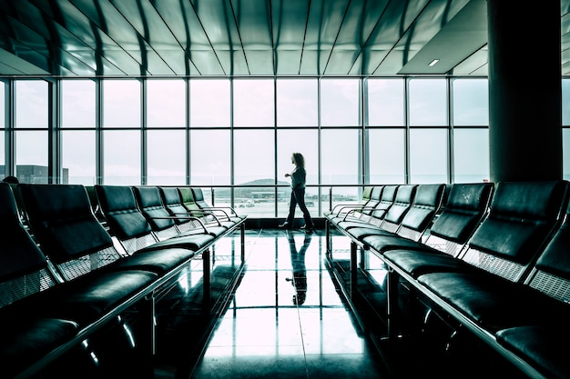 Woman walking at the airport gate waiting the flight start for business or vacation activity - delay fly or canceled - rights and insurance for travelers concept