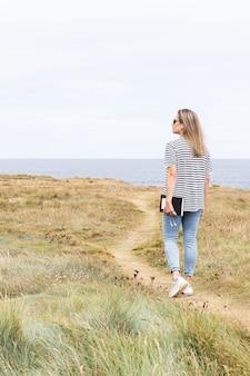 海の前の道を歩いている女性