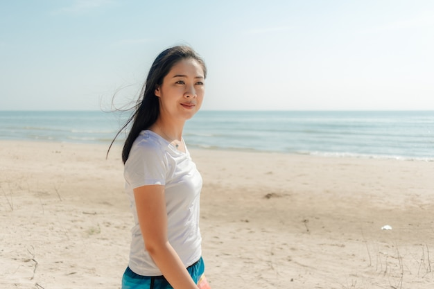 Woman walking along the beach under the sunny day of summer.