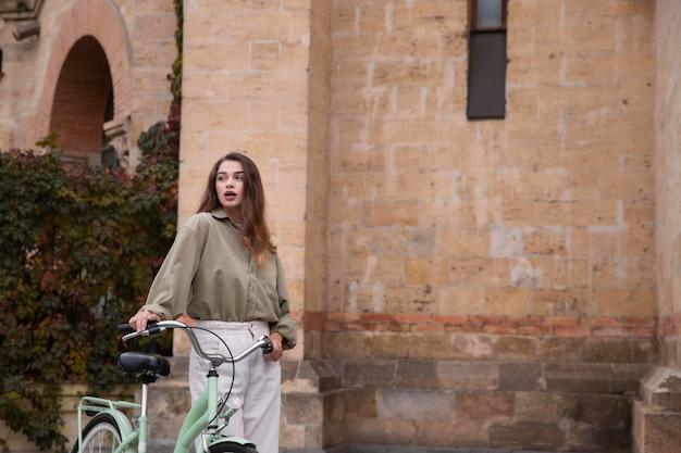 복사 공간 야외에서 자전거를 따라 걷는 여자