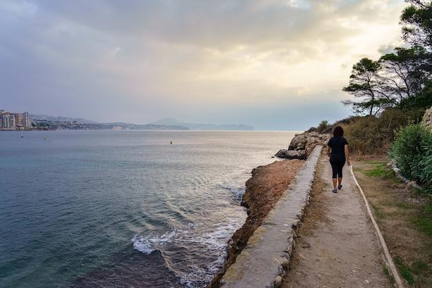 夏の日の日没で海の崖に沿って歩く女性。