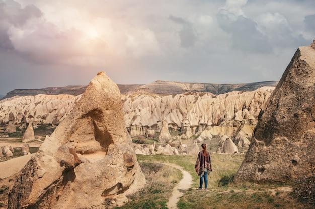 Женщина гуляя и наслаждаясь ландшафтом горы cappadocia