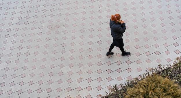 Женщина гуляет и разговаривает по мобильному телефону