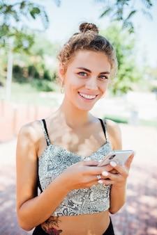 日当たりの良い夏の日に通りでスマートフォンを使用して歩いている女性