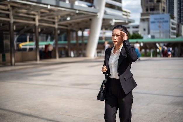 街のビジネス問題について頭痛を歩く女性