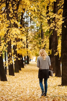 Woman walking away in autumn park with golden trees full height