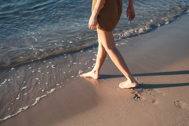 Woman walking barefoot on the beach in the morning at summertime