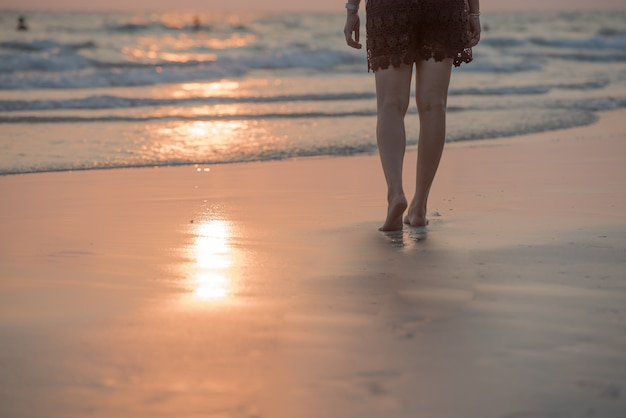Woman walking on the beach at sunset.