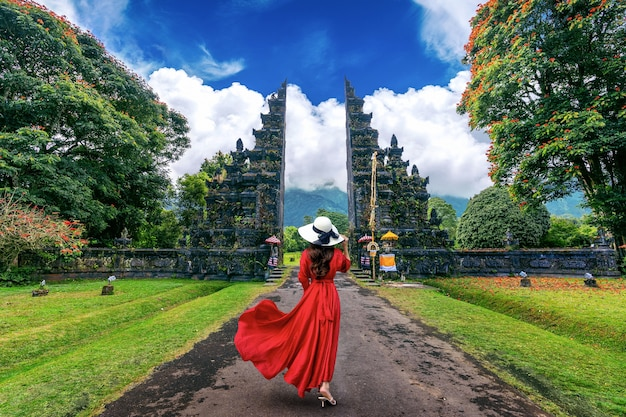 Woman walking at big entrance gate, bali in indonesia