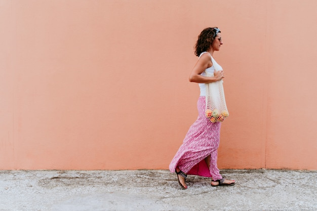 Woman walking by the city, holding a cotton bag with fruit.