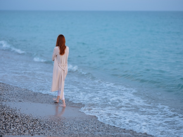 Woman walking by the ocean rest freedom romance. high quality photo