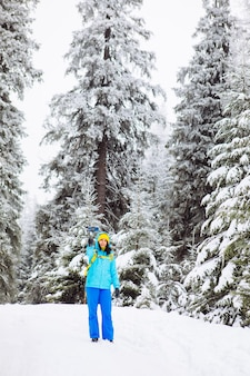 Woman walking by snowed forest shooting on the phone copy space