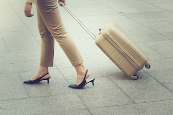 Woman walking carrying a suitcase