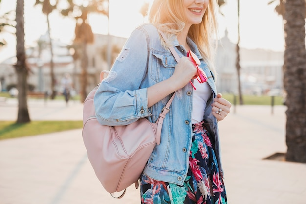 Woman walking in city street in stylish denim oversize jacket, holding pink leather backpack