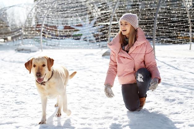 冬の日に屋外でかわいい犬を散歩する女性。
