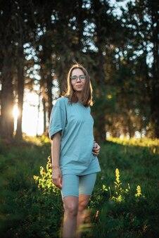 夏の森エリアの早い段階で歩く女性
