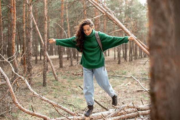 Woman walking on fallen tree