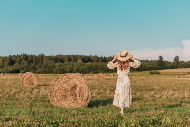 Woman walking in field with haystacks