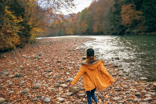 Woman walking in the forest along the river autumn travel