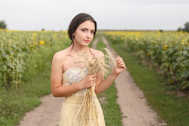 Woman walking in golden dried grass field. natural portrait beauty. beautiful girl keeping wheat crop in her hands while in yellow wheat field