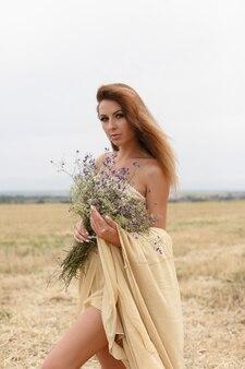 Woman walking in golden dried grass field. natural portrait beauty. beautiful girl in a wheat field. young woman in a beige dress holding a bouquet of wildflowers.