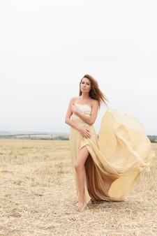 Woman walking in golden dried grass field. natural portrait beauty. beautiful girl in a wheat field