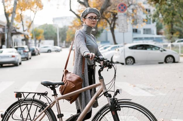 Donna che cammina accanto alla sua bicicletta