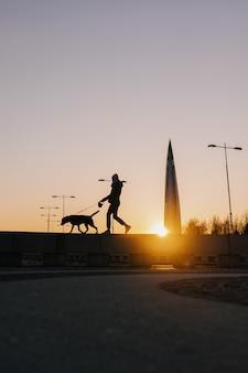現代の建物を背景に美しい夕日の日没で彼女の犬を歩く女性