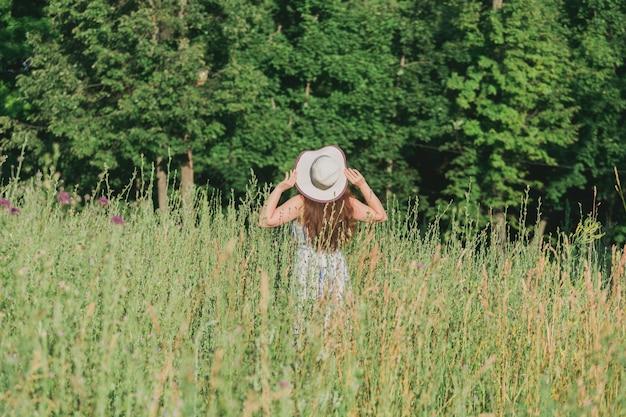 여름 화창한 날 뒷면보기에 필드에 걷는 여자