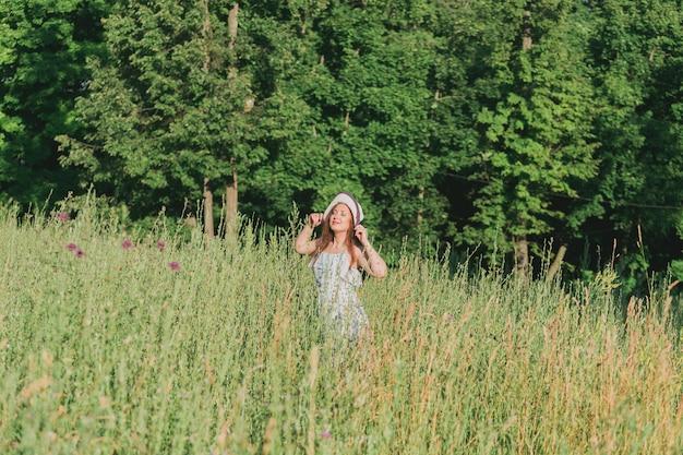 여름 화창한 날에 필드에 걷는 여자.