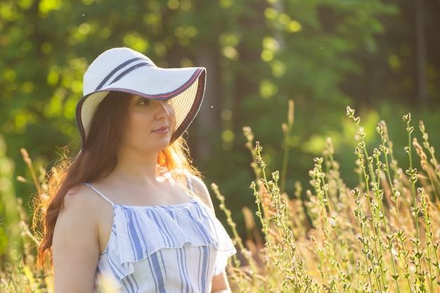 여름 화창한 날에 필드에서 산책 하는 여자.
