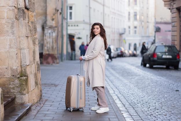 Женщина гуляет по новому городу с телефоном в руках и чемоданом