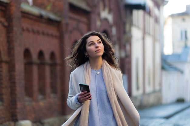 그녀의 손에 전화와 가방으로 새로운 도시에서 걷는 여자