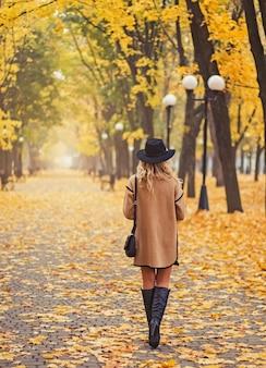 Женщина гуляет в красивом осеннем парке