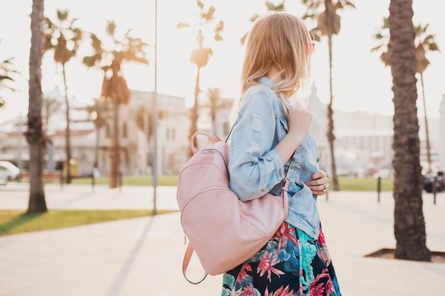핑크 가죽 배낭을 들고 세련된 데님 특대 재킷에 도시 거리를 걷는 여자