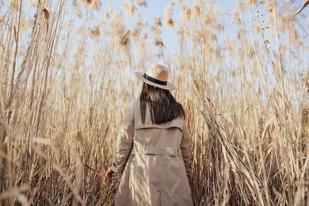 Женщина гуляет по сухому камышу