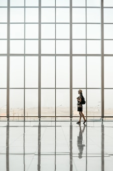 Woman walking in front of a giant glass windows