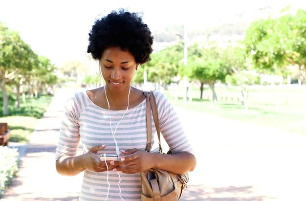 Женщина, ходить в парке, слушать музыку на телефоне