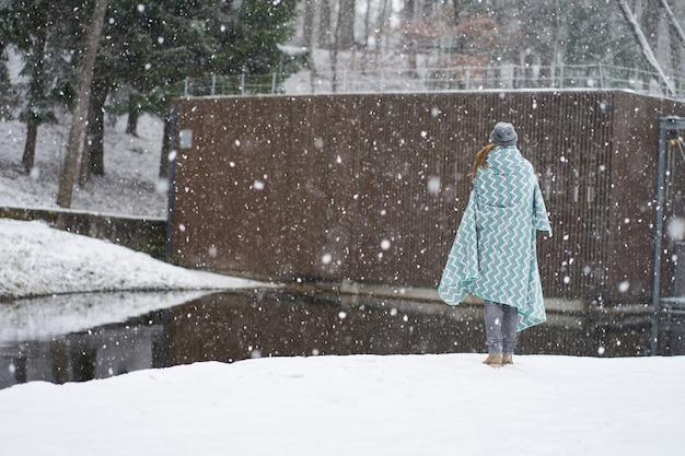 毛布で覆われた雪の公園を歩く女性