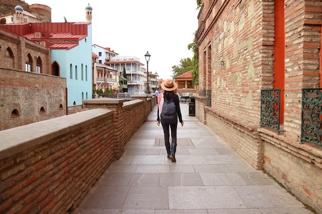 Женщина гуляет в красивом старом городе тбилиси