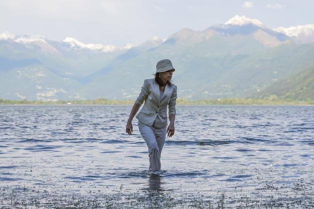 Женщина гуляет по озеру с высокими горами на заднем плане